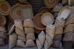In this Saturday, June 22, 2019 photo, almonds and baskets are displayed outside a shop in Srinagar, Indian controlled Kashmir.  California almond farmers are facing long-term uncertainty in the wake of new tariffs on exports to India, the state's top market for almonds. Farmers and experts predict the tariffs, leveled by India amid trade tensions with the United States, will complicate almond sales abroad. The tariffs may result in increased almond prices for buyers, so farmers expect to sell less.  (AP Photo/ Dar Yasin)