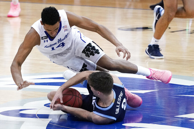 Seton Hall guard Jared Rhoden (14) and Villanova guard Collin Gillespie (2) fight for the ball during the second half of an NCAA college basketball game, Saturday, Jan. 30, 2021, in Newark, N.J. (AP Photo/Mary Altaffer)