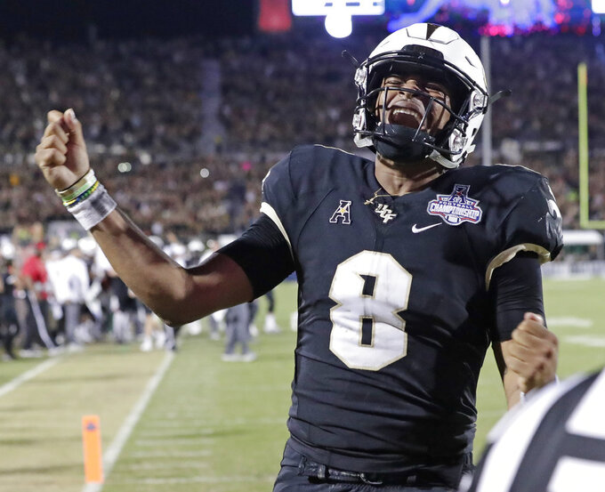 Central Florida quarterback Darriel Mack Jr. (8) celebrates after scoring the go ahead touchdown against Memphis during the second half of the American Athletic Conference championship NCAA college football game, Saturday, Dec. 1, 2018, in Orlando, Fla. (AP Photo/John Raoux)