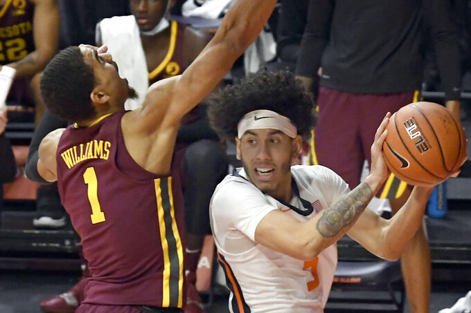 Illinois guard Andre Curbelo (5) puts the ball up as Minnesota's guard Tre' Williams (1) defends in the first half of an NCAA college basketball game Tuesday, Dec. 15, 2020, in Champaign, Ill. (AP Photo/Holly Hart)