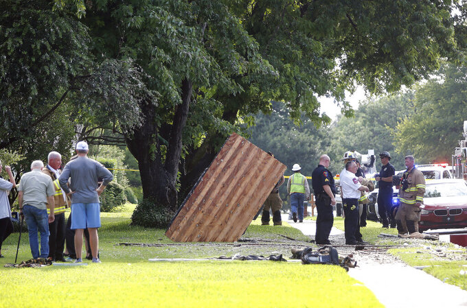 Neighbors and first responders stand near a piece of roofing, center, that landed in a yard across the street from a home that exploded at about 4:45 p.m. in the 4400 block of Cleveland Drive in Plano, Texas, Monday, July 19, 2021. (Stewart F. House/The Dallas Morning News via AP)