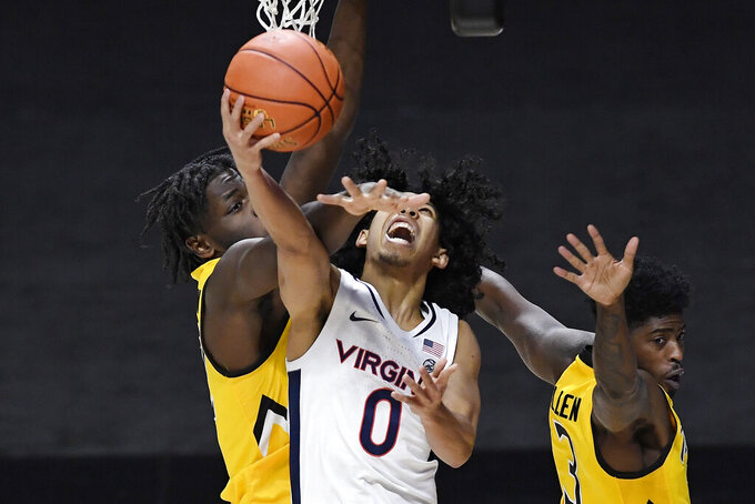 Virginia's Kihei Clark, center, is fouled by Towson's Charles Thompson, left, as Towson's Cam Allen, right, defends in the second half of an NCAA college basketball game, Wednesday, Nov. 25, 2020, in Uncasville, Conn. (AP Photo/Jessica Hill)