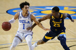 UCLA guard Jules Bernard, left, is defended by Marquette forward Jamal Cain during the second half of an NCAA college basketball game Friday, Dec. 11, 2020, in Los Angeles. (AP Photo/Ashley Landis)