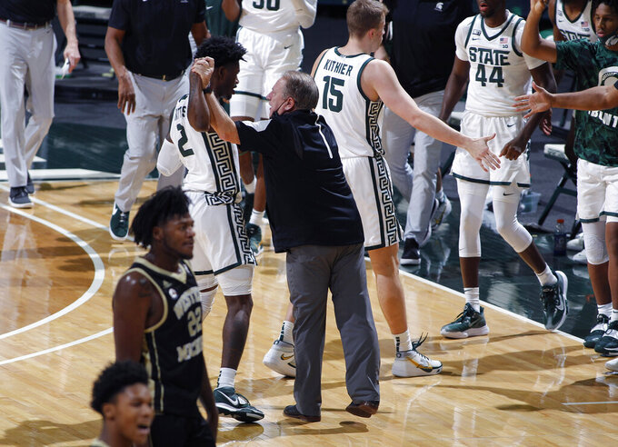 Michigan State coach Tom Izzo, center, congratulates Rocket Watts (2) during a timeout during the first half of an NCAA college basketball game against Western Michigan, Sunday, Dec. 6, 2020, in East Lansing, Mich. (AP Photo/Al Goldis)