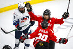 Canada's Brianne Jenner, right rear, celebrates her goal with Marie-Philip Poulin, as United States' Megan Bozek skates away during the second period of the IIHF hockey women's world championships title game in Calgary, Alberta, Tuesday, Aug. 31, 2021. (Jeff McIntosh/The Canadian Press via AP)