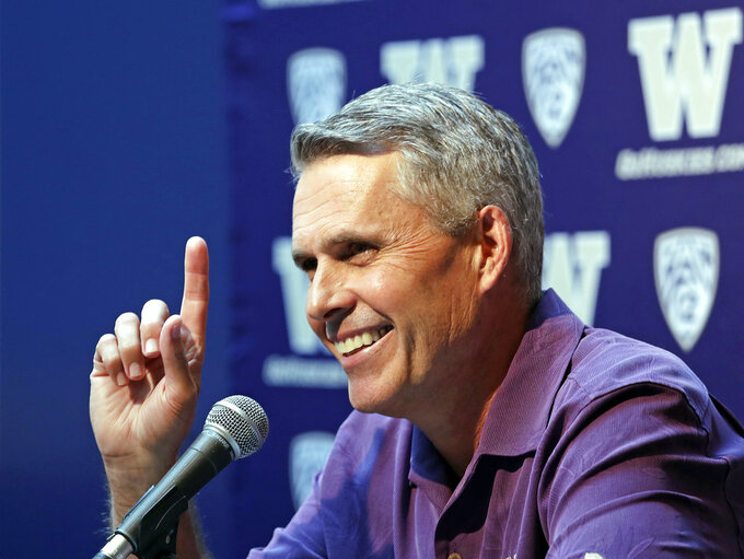 Washington NCAA college head football coach Chris Petersen points skyward in response to hearing Blue Angels jets soar nearby as he speaks at a news conference Thursday, Aug. 2, 2018, in Seattle. Petersen hates expectations, so he's likely loathing Washington being the overwhelming favorite in the Pac-12 and likely top 10 when the preseason AP poll comes out. The Huskies open fall camp on Friday in preparation for the Sept. 1 opener against Auburn. (AP Photo/Elaine Thompson)