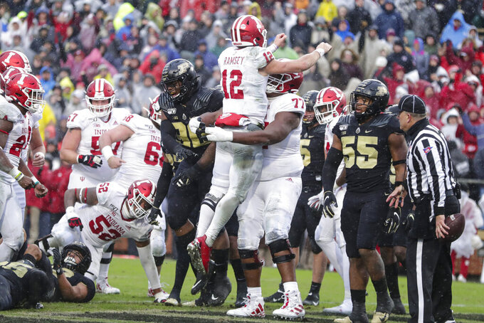 Indiana quarterback Peyton Ramsey (12) celebrates a touchdown against Purdue with offensive lineman Caleb Jones (77) during the first half of an NCAA college football game in West Lafayette, Ind., Saturday, Nov. 30, 2019. (AP Photo/Michael Conroy)