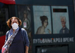 A woman wearing a face mask to protect against coronavirus walks in downtown Belgrade, Serbia, Monday, July 13, 2020. Health authorities are warning that Serbian hospitals are almost full due to the latest surge. (AP Photo/Darko Vojinovic)