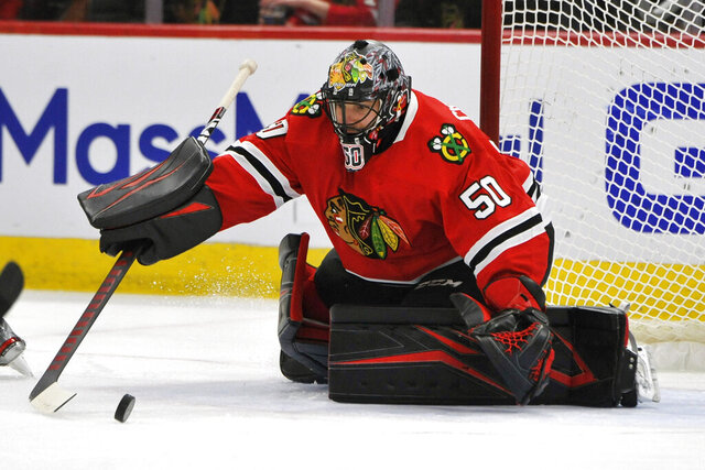 FILE - In this March 11, 2020 file photo, Chicago Blackhawks goalie Corey Crawford (50) makes a save during the first period of an NHL hockey game against the San Jose Sharks in Chicago.  Crawford practiced Saturday, July 25,  after he missed the start of training camp because he tested positive for COVID-19. The 35-year-old said he was in quarantine at his place in Chicago.  (AP Photo/Paul Beaty, File)