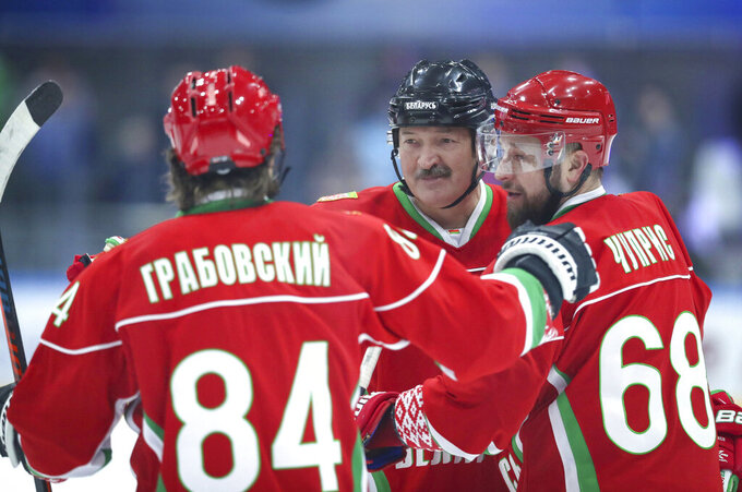 FILE - In this photo taken on Saturday, March 28, 2020, Belarusian President Alexander Lukashenko, centre, takes part in a hockey match during Republican amateur competitions in Minsk, Belarus. From the U.S. president to the British prime minister's top aide and far beyond, leading officials around the world are refusing to wear masks or breaking confinement rules meant to protect their populations from the coronavirus and slow the pandemic. While some are punished when they're caught, or publicly repent, others shrug off the violations as if the rules don't apply to them. (Andrei Pokumeiko/BelTA Pool Photo via AP, File)