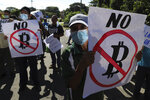 Farmers hold signs emblazoned with messages against the country adopting Bitcoin as legal tender, during a protest along  the Pan-American Highway, in San Vicente, El Salvador, Tuesday, Sept. 7, 2021. El Salvador became the first country to adopt Bitcoin as legal tender Tuesday, but the rollout stumbled in its first hours and President Nayib Bukele informed that the digital wallet used for transactions was not functioning. (AP Photo/Salvador Melendez)