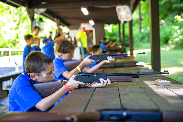 Sylas Sekely, 8, of Monroeville, Pa., concentrates as he prepares to shoot at a target with a BB gun Thursday, June 11, 2020, at Camp Guyasuta in Sharpsburg, Pa. Camp Guyasuta's STEM Adventure Day Camp started for the summer on Monday, one of a handful of camps to open with adjusted protocols due to the COVID-19 pandemic. (Michael M. Santiago/Pittsburgh Post-Gazette via AP)