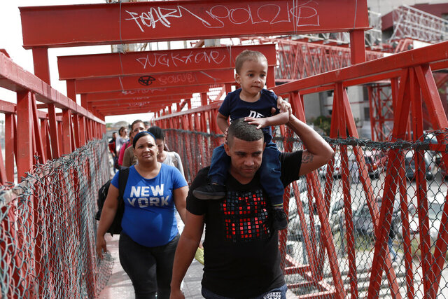 FILE - In this April 29, 2019, file photo, Cuban migrants are escorted in Ciudad Juarez, Mexico, by Mexican immigration officials as they cross the Paso del Norte International bridge to be processed as asylum seekers on the U.S. side of the border. Newly unsealed court documents show that many U.S. holding cells along the Mexican border were less than half-full, or even empty, during an unprecedented surge of asylum-seeking Central American families. The documents cast doubt on the Trump administration's claims that people had to wait in Mexico because there weren't enough resources to accommodate them. (AP Photo/Christian Torres, File)