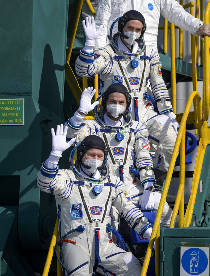 In this image provided by NASA, Russian cosmonaut Pyotr Dubrov, top, NASA astronaut Mark Vande Hei, middle, and Russian cosmonaut Oleg Novitskiy wave farewell prior to boarding the Soyuz MS-18 spacecraft for launch, Friday, April 9, 2021, at the Baikonur Cosmodrome in Kazakhstan. The astronaut and cosmonauts are scheduled to launch aboard the Soyuz MS-18 spacecraft Friday, to rendezvous with the International Space Station.(Bill Ingalls/NASA via AP)
