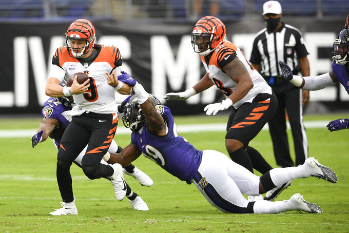 Cincinnati Bengals quarterback Joe Burrow (9) avoids a tackle by Baltimore Ravens outside linebacker Matt Judon (99) while scrambling for yardage during the first half of an NFL football game, Sunday, Oct. 11, 2020, in Baltimore. (AP Photo/Nick Wass)