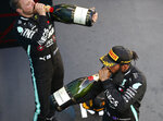 Race winner, Mercedes driver Lewis Hamilton of Britain, front, drinks champagne with third placed Mercedes driver Valtteri Bottas of Finland after the Formula One Grand Prix at the Barcelona Catalunya racetrack in Montmelo, Spain, Sunday, Aug. 16, 2020. (Bryn Lennon, Pool via AP)