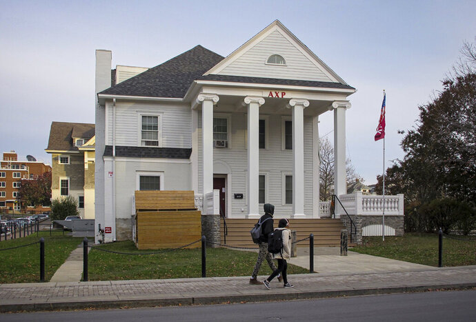Youngsters walk past the residence for the Syracuse University chapter of Alpha Chi Rho, Thursday, Nov. 21, 2019, in Syracuse, N.Y. The fraternity has been suspended pending the investigation of a black student's complaint last week that she was called a racial slur as she walked by a group of people identified by the university as fraternity members and their guests. It was one of more than a dozen racist incidents that have plagued the university since Nov. 7, including several reports of graffiti targeting black and Jewish students, Asians and Native Americans. (AP Photo/Carolyn Thompson)