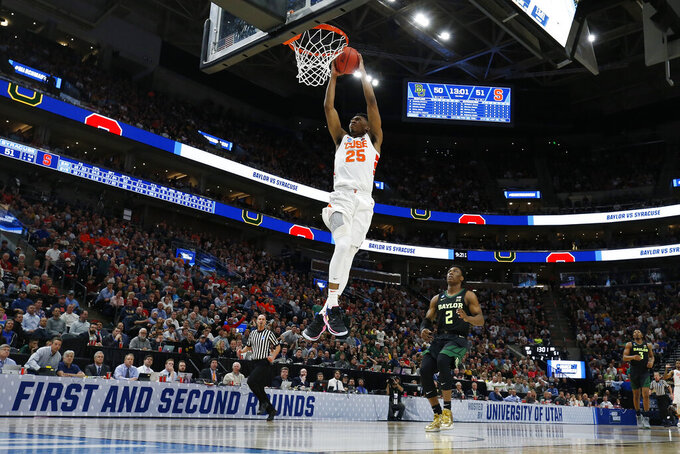Syracuse guard Tyus Battle (25) dunks in front of Baylor guard Devonte Bandoo (2) during the second half of a first-round game in the NCAA men's college basketball tournament Thursday, March 21, 2019, in Salt Lake City. (AP Photo/Jeff Swinger)