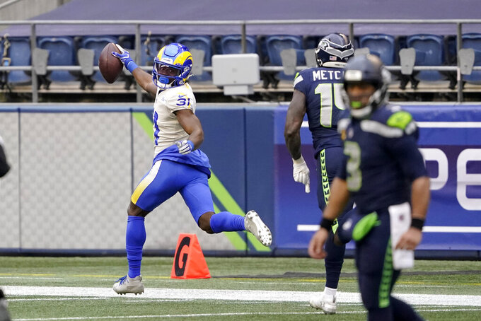Los Angeles Rams defensive back Darious Williams (31) looks back as he scores on an interception from Seattle Seahawks quarterback Russell Wilson, right, during the first half of an NFL wild-card playoff football game, Saturday, Jan. 9, 2021, in Seattle. (AP Photo/Ted S. Warren)