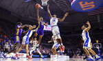 LSU guard Marlon Taylor (14) shoots while defended by Florida center Kevarrius Hayes (13) during the second half of an NCAA college basketball game in Gainesville, Fla., Wednesday, March 6, 2019. (AP Photo/Gary McCullough)