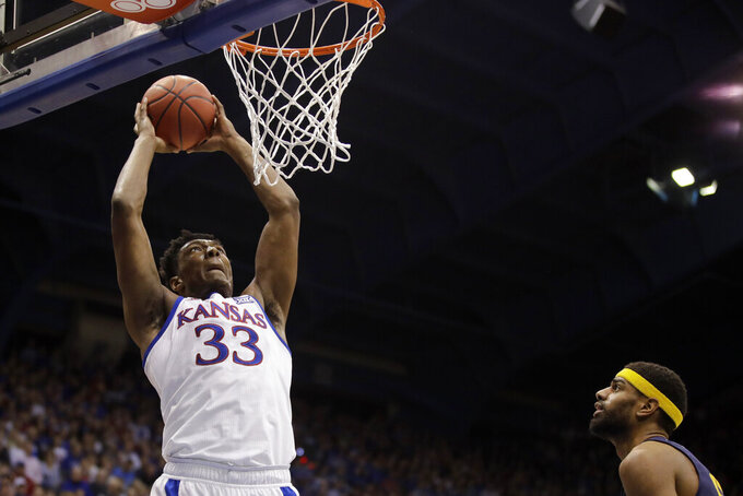 Kansas forward David McCormack (33) gets past East Tennessee State forward Jeromy Rodriguez, right, to put up a shot during the first half of an NCAA college basketball game Tuesday, Nov. 19, 2019, in Lawrence, Kan. (AP Photo/Charlie Riedel)
