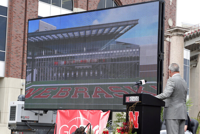 Nebraska Athletic Director Bill Moos, right, presents an artists rendering of a new planned $150 million football training facility adjacent to Memorial Stadium, during an NCAA college football news conference, Friday, Sept. 27, 2019, in Lincoln, Neb.. (AP Photo/Nati Harnik)