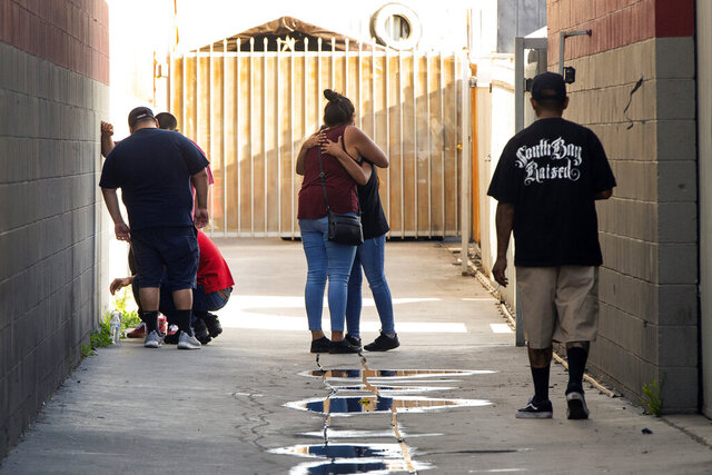 FILE - In this Friday, June 19, 2020, file photo, relatives of victim Andres Guardado, 18, who was fatally shot by a Los Angeles County sheriff's deputy, embrace as they tour the site of the shooting inside an auto shop in Gardena, Calif. The Los Angeles County Sheriff's Department said Saturday, June 20 that it is examining footage from security cameras that might have recorded the fatal shooting after deputies spotted Guardado with a gun and he ran. (AP Photo/Damian Dovarganes, File)