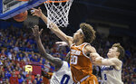 Texas forward Jericho Sims (20) fights for a rebound again Kansas Jayhawks Marcus Garrett (0) and Kansas guard Christian Braun (2) during the second half of an NCAA college basketball game in Lawrence, Kan., Monday, Feb. 3, 2020. (AP Photo/Reed Hoffmann