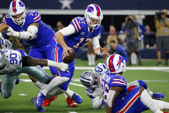 Dallas Cowboys defensive end DeMarcus Lawrence (90) pressures Buffalo Bills quarterback Josh Allen (17) out of the pocket as offensive tackle Cody Ford (70) looks on in the first half of an NFL football game in Arlington, Texas, Thursday, Nov. 28, 2019. (AP Photo/Michael Ainsworth)