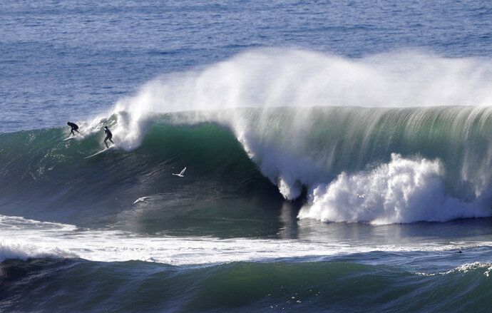 FILE - In this Dec. 21, 2016 file photo two surfers share a wave at the Mavericks surf spot off Pillar Point Harbor in Half Moon Bay, Calif. California Gov. Jerry Brown announced Monday, Aug. 20, 2018 that he signed a bill making surfing the official state sport. (AP Photo/Marcio Jose Sanchez,File)