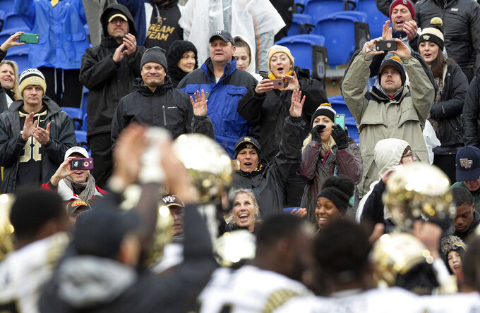 Wake Forest fans celebrate with players following a 59-7 victory over Duke in an NCAA college football game in Durham, N.C., Saturday, Nov. 24, 2018. (AP Photo/Ben McKeown)
