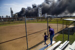 Cloud of smoke in the background from the TPC Group Port Neches Operations explosion is visible from a little league baseball park on Wednesday, Nov. 27, 2019, in Port Neches, Texas. (Marie D. De Jesús/Houston Chronicle via AP)