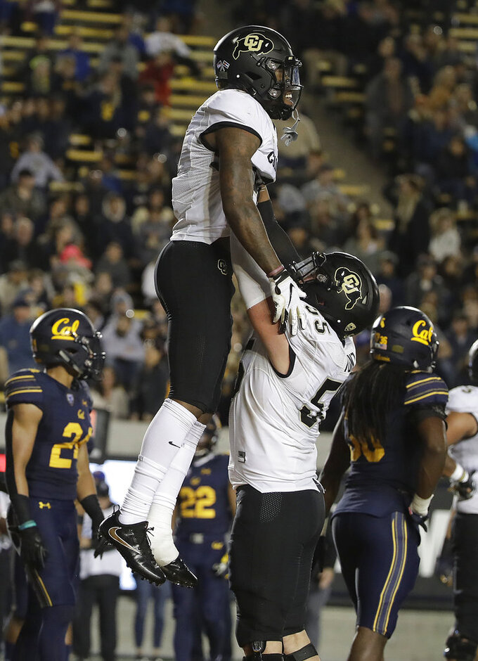 Colorado wide receiver Juwann Winfree, top, celebrates with offensive lineman Brett Tonz after scoring against California during the second half of an NCAA college football game in Berkeley, Calif., Saturday, Nov. 24, 2018. California won, 33-21. (AP Photo/Jeff Chiu)