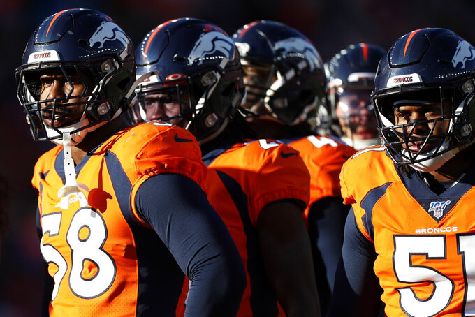 Denver Broncos outside linebacker Von Miller, left, and members of the defense look on during the first half of an NFL football game against the Oakland Raiders, Sunday, Dec. 29, 2019, in Denver. (AP Photo/David Zalubowski)