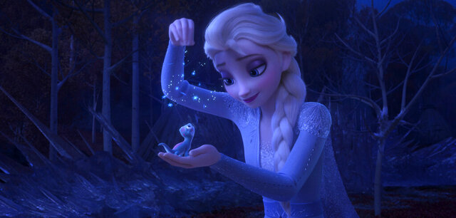 This image released by Disney shows Elsa, voiced by Idina Menzel, sprinkling snowflakes on a salamander named Bruni in a scene from the animated film,