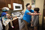 """In this July 28, 2021 photo, Christina Darling and her sons, Brennan, 4, left, and Kayden, 10, prepare a snack at home in Nashua, N.H. Darling and her family have qualified for the expanded child tax credit, part of President Joe Biden's $1.9 trillion coronavirus relief package. """"Every step closer we get to a livable wage is beneficial. That is money that gets turned around and spent on the betterment of my kids and myself,"""" said Darling, a housing resource coordinator who had been supplementing her $35,000-a-year salary with monthly visits to the Nashua Soup Kitchen and Shelter's food pantry. (AP Photo/Elise Amendola)"""