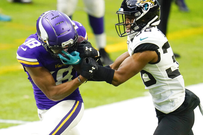 Minnesota Vikings wide receiver Justin Jefferson, left, catches a pass in front of Jacksonville Jaguars cornerback Luq Barcoo, right, during the second half of an NFL football game, Sunday, Dec. 6, 2020, in Minneapolis. (AP Photo/Jim Mone)