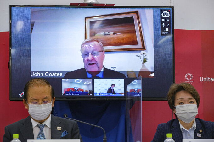 FILE - In this May 21, 2021, file photo, CEO of the Tokyo 2020 Toshiro Muto, left, and President of the Tokyo 2020 Seiko Hashimoto, right, listen to IOC Vice President  John Coates, (on screen), delivering a speech during the Tokyo 2020 IOC Coordination Commission press conference in Tokyo. Comments from Coates saying the Tokyo Olympics will go on even if the city is under a state of emergency have stirred a backlash in Japan.  Coates made the statement a few days ago. He repeated what the IOC and local organizers have been staying, but his tone was almost defiant and has stirred things up. (Nicolas Datiche/Pool Photo via AP, File)