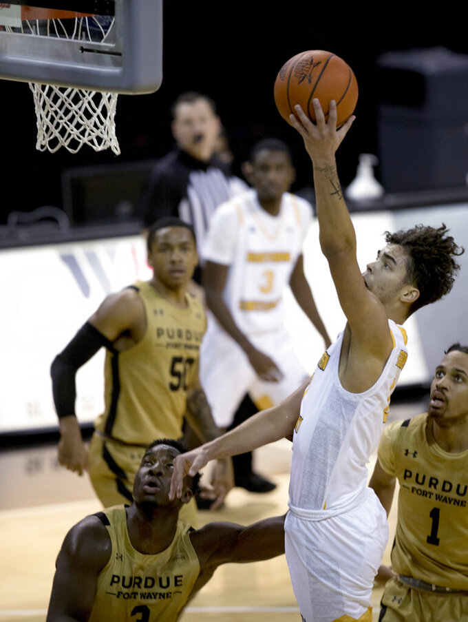 Northern Kentucky guard Trey Robinson (0) lays the ball up as Purdue-Fort Wayne forward Ra Kpedi (3) watches during the first half of an NCAA college basketball game Friday, Jan. 1, 2021, in Highland Heights, Ky. (Albert Cesare/The Cincinnati Enquirer via AP)