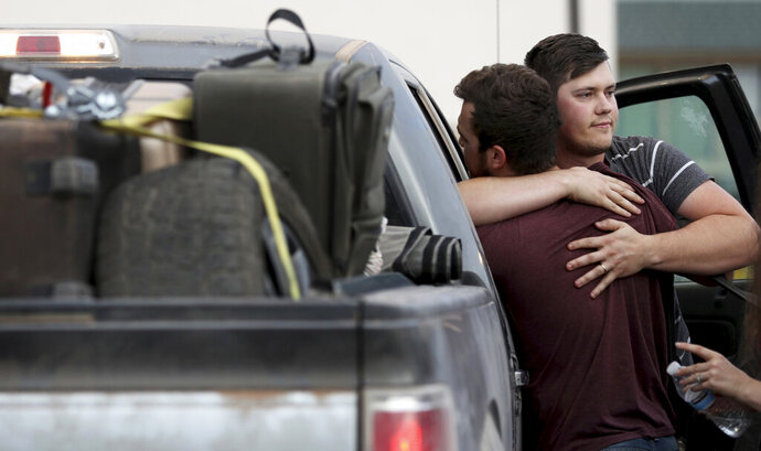 Cole Langford, left, and Hayden Spenct, of the Mormon colony in La Mora, Mexico, hug during a rendezvous in a gas station in Douglas, Ariz., Saturday, Nov. 9, 2019. Family and friends said goodbye Saturday to the last victim of a cartel ambush that killed nine American women and children from a Mormon community in northern Mexico where cartels have disrupted an otherwise peaceful, rural existence. (Kelly Presnell/Arizona Daily Star via AP)