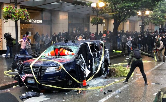 Protesters gather around a destroyed Seattle police vehicle Saturday, May 30, 2020, in downtown Seattle. Protests continue across the country over the death of George Floyd, a black man who died after being restrained by Minneapolis police officers on May 25. (Amanda Snyder/The Seattle Times via AP)