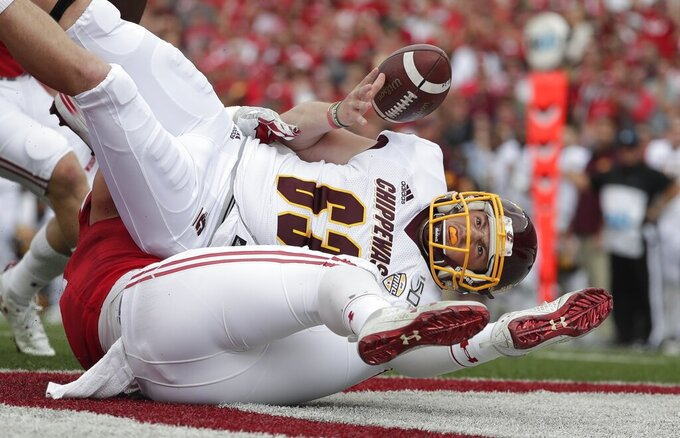 Central Michigan place kicker Brady Buell loses the ball as he is hit during the first half of an NCAA college football game against Wisconsin Saturday, Sept. 7, 2019, in Madison, Wis. The play resulted in a safety. (AP Photo/Morry Gash)