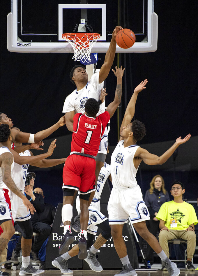Old Dominion forward Kalu Ezikpe blocks a shot by Western Kentucky guard Lamonte Bearden (1) as Old Dominion's Jason Wade (1) also defends during the second half of an NCAA college basketball game for the Conference USA men's tournament championship Saturday, March 16, 2019, in Frisco, Texas. Old Dominion won 62-56. (AP Photo/Jeffrey McWhorter)