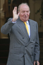 FILE - In this file photo dated Saturday, March 10, 2018, Spain's emeritus King Juan Carlos waves upon his arrival to the Academia Diplomatica de Chile, in Santiago.  Spain's royal family's website on Monday Aug. 3, 2020, published a letter from Spain's former monarch, King Juan Carlos I, saying he is leaving Spain to live in another country, amidst a financial scandal. (AP Photo/Esteban Felix, FILE)