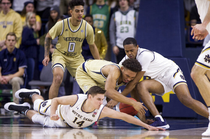 Notre Dame's Nate Laszewski (14) and D.J. Harvey, right, compete for a loose ball with Georgia Tech's James Banks III, center, during the first half of an NCAA college basketball game Sunday, Feb. 10, 2019, in South Bend, Ind. (AP Photo/Robert Franklin)