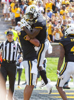 Missouri tight end Albert Okwuegbunam, left, is hugged by teammate Jalen Knox, top, after Okwuegbunam scored a touchdown during the first half of an NCAA college football game against West Virginia Saturday, Sept. 7, 2019, in Columbia, Mo. Missouri won the game 38-7.(AP Photo/L.G. Patterson)