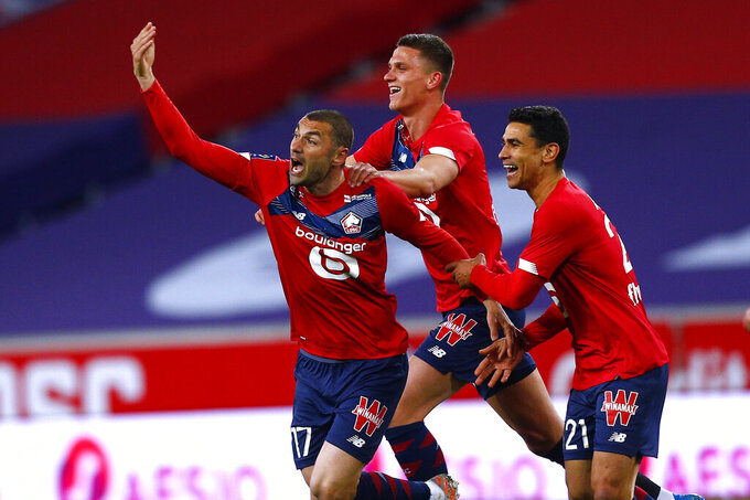 Lille's Burak Yilmaz, left, reacts after scoring during their French League One soccer match between Lille and Nice in Villeneuve d'Ascq, northern France, Saturday May 1, 2021. (AP Photo/Michel Spingler)