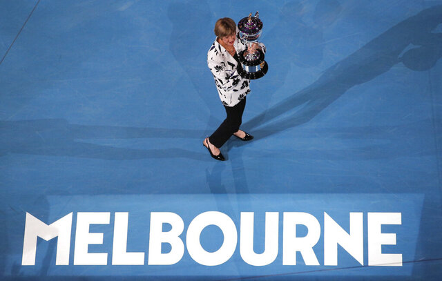 Former Australian Open champion Margaret Court holds up the women's Australian Open trophy, the Daphne Ackhurst Memorial Cup, as her 50th anniversary of her Grand Slam is celebrated at the Australian Open tennis championship in Melbourne, Australia, Monday, Jan. 27, 2020. (AP Photo/Andy Wong)