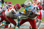 Kansas City Chiefs defensive tackle Mike Pennel (64) and defensive end Tanoh Kpassagnon (92) tackle Miami Dolphins running back DeAndre Washington (31), during the second half of an NFL football game, Sunday, Dec. 13, 2020, in Miami Gardens, Fla. (AP Photo/Wilfredo Lee)