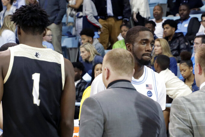 Wofford's Chevez Goodwin (1) walks past North Carolina's  Brandon Robinson, third from left, at the end of an NCAA college basketball game in Carmichael Arena in Chapel Hill, N.C., Sunday, Dec. 15, 2019. (AP Photo/Chris Seward)
